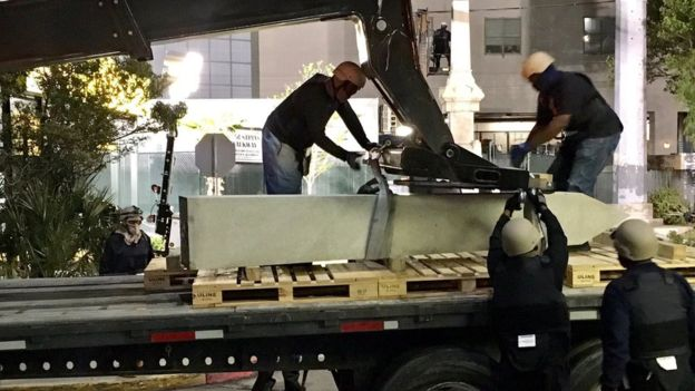Trabajadores de Nueva Orleans con el rostro cubierto preparando la remoción del monumento de Liberty Place. EPA