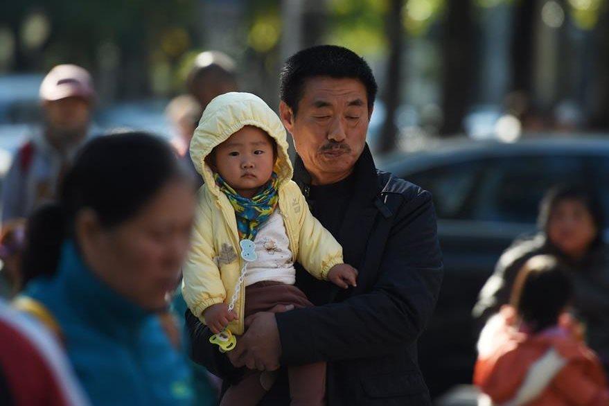 Un hombre lleva en brazos a un niño en las calles de Beijing. (Foto Prensa Libre: AFP).