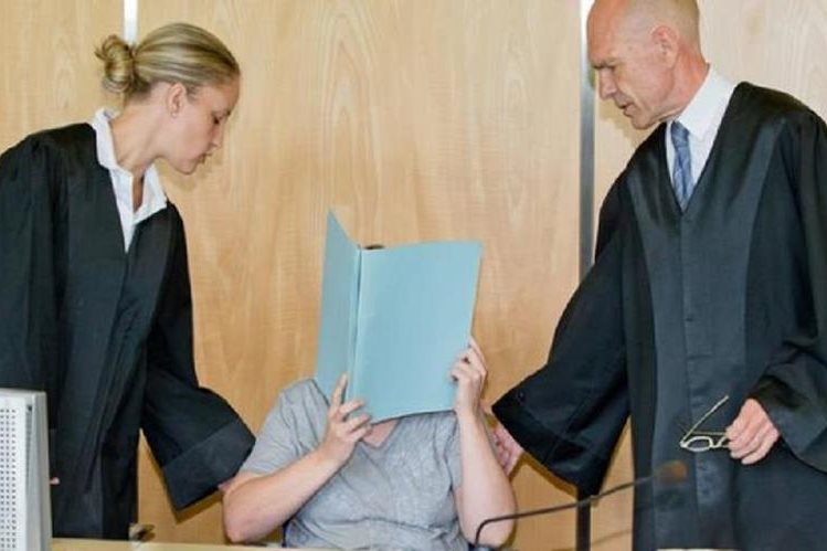 Alemana se cubre el rostro al escuchar la condena por la muerte de ocho bebés.(DPA).
