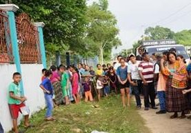 Vecinos de Las Pozas, Sayaxché, observan el lugar donde quedó una de las dos víctimas mortales del ataque armado ocurrido este sábado. (Foto Prensa Libre: Rigoberto Escobar)