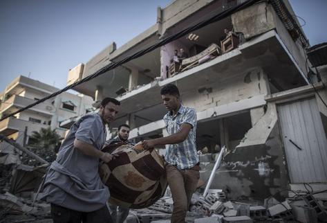 Varios palestinos se llevan objetos rescatados de entre los escombros de una casa destruida por un ataque aéreo nocturno del Ejército israelí en la ciudad de Gaza (Foto Prensa Libre: EFE)