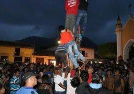 Un grupo de jóvenes hacen el intento de alcanza la bandera roja al final del palo. (Foto Prensa Libre: Renato Melgar)