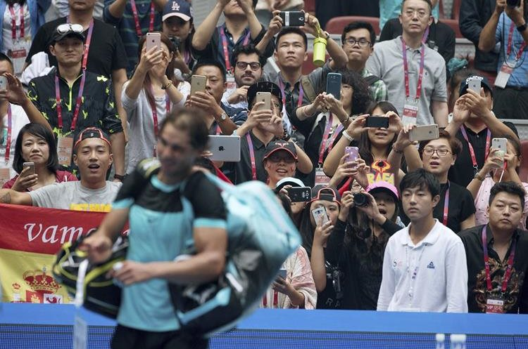 Spectators take pictures of Rafael Nadal of Spain leaving the court after defeating Wu Di of China in the first round men