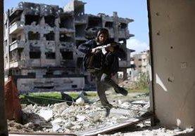 Un combatiente rebelde trata de ponerse a salvo durante un enfrentamiento en las afueras de Damasco, Siria. (Foto Prensa Libre: AFP).