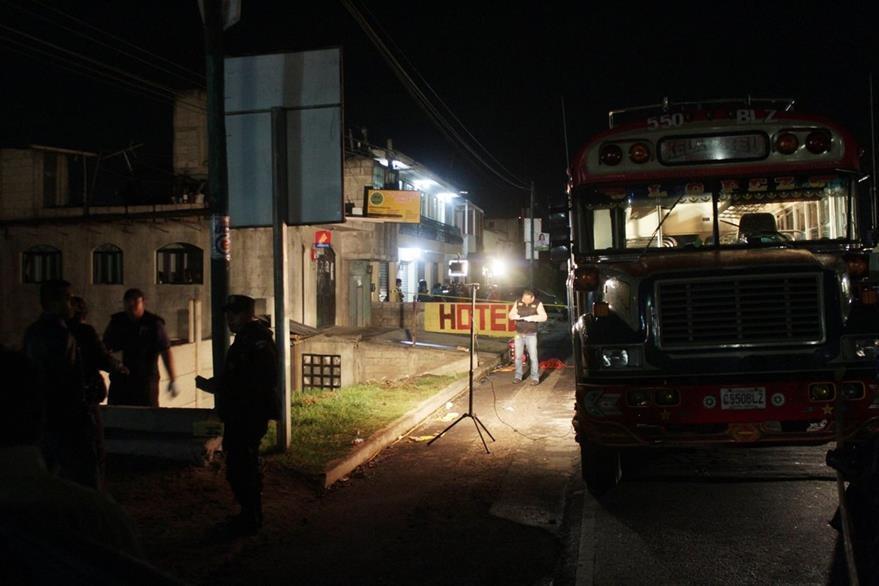 Un autobús atacado a balazos por presuntos extorsionistas, es resguardado por agentes de la PNC en Quetzaltenango. (Foto HemerotecaPL)