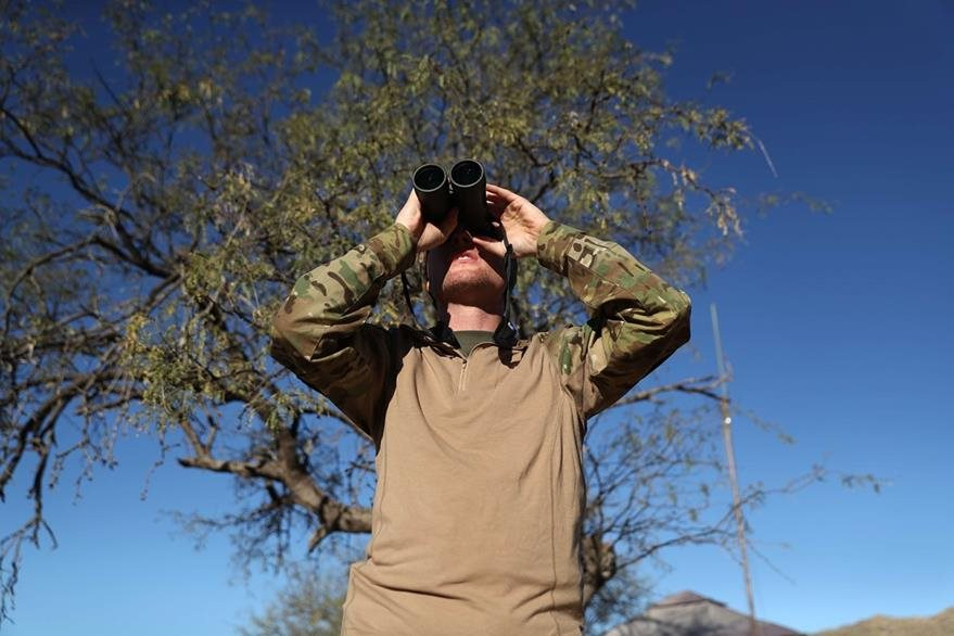 Un guardia fronterizo estadounidense vigila con largavistas la frontera entre EE. UU. y México. (Foto Prensa Libre: AFP).