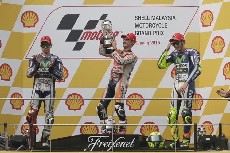 Dani Pedrosa levanta el trofeo en el podio junto a Jorge Lorenzo y Valentino Rossi. (Foto Prensa Libre: EFE)