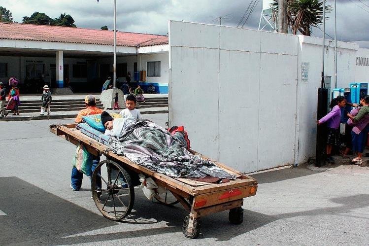 Luis Borja lleva al hospital a su esposa, Blanca Eluvia Delgado, quien padecía diabetes, en su carreta de madera, el 17 de marzo. (Foto Prensa Libre: Víctor Chamalé)