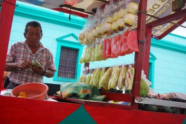 Francisco Méndez prepara mangos que comprarán estudiantes de una escuela cuando salgan de clases. (Foto Prensa Libre: Mario Morales)