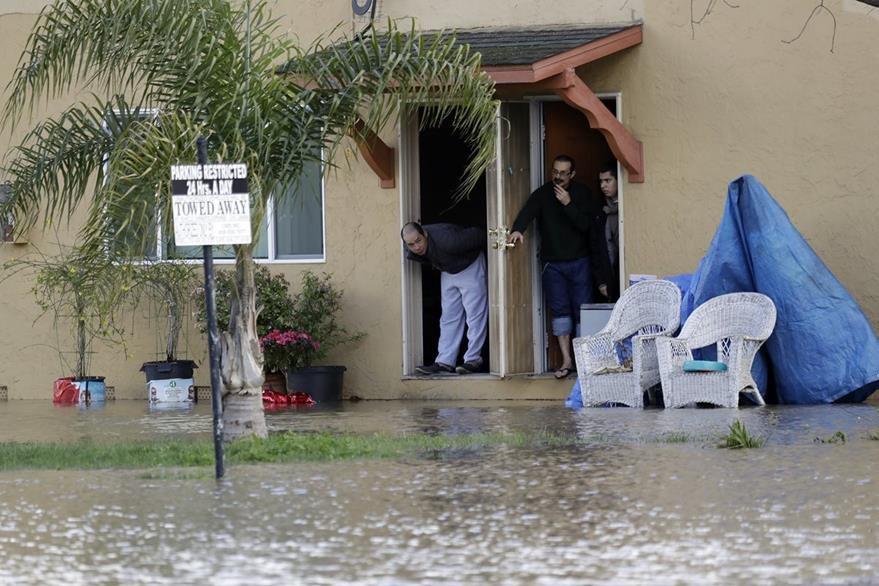 Vecinos observan desde la inundación en un complejo de apartamentos en San José, California.(AP).