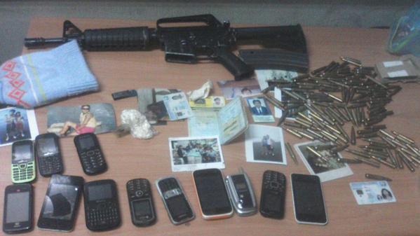 Un fusil, municiones, teléfonos y documentos personales, fueron incautados al grupo. (Foto Prensa Libre: PNC)