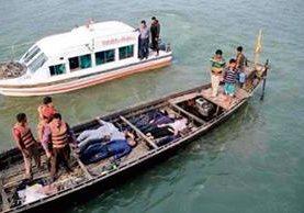 Oficiales bengalíes  cargan cuerpos de víctimas del naufragio de un ferry de pasajeros en Manikganj. AFP