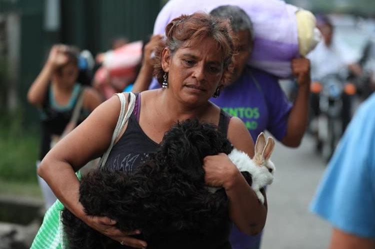 Sin olvidar a sus mascotas una mujer corre hacia el centro de Escuintla.