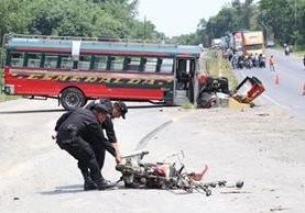 Agentes de la Policía Nacional Civil retiran la motocicleta de Rogers Miranda Santizo, quien murió al colisionar en contra de un bus extraurbano. (Foto Prensa Libre: Cristian Icó Soto)
