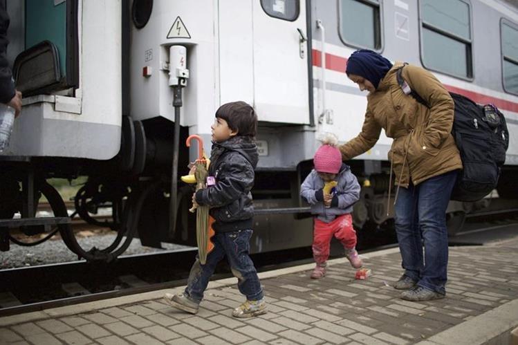 Refugiados suben a un tren en la estación de Tovarnik, Croacia. (Foto Prensa Libre: EFE).