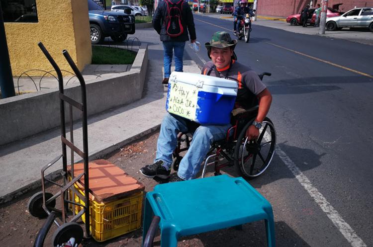 Alex Guzmán, víctima de accidente de motocicleta, trabaja nueve horas al día en su venta de cocos. (Foto Prensa Libre: Óscar García).