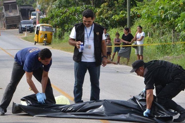 Autoridades retiran el cuerpo sin vida de Oscar René Tec Sacul de la calle. (Foto Prensa Libre: Rigoberto Escobar)