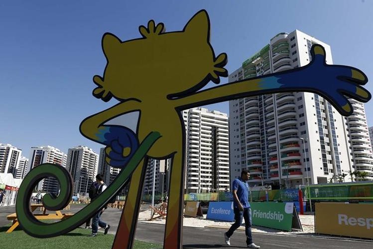 Fotografía donde se ve la silueta de la mascota olímpica de Río 2016 Vinícius frente a la Villa que albergará a los deportistas que disputarán los Juegos. (Foto Prensa Libre: EFE)