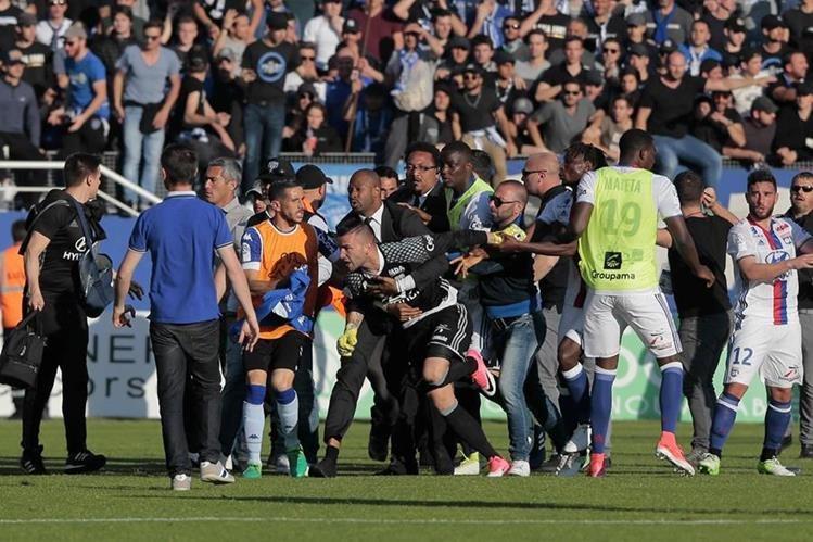 El portero del Lyon, Anthony Lopes es sostenido por un agente de seguridad, mientras los aficionados del Bastia intentan alcanzarlo. (Foto Prensa Libre: AFP)