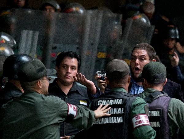 Dos legisladores de oposición discuten con los oficiales de la Guardia Nacional en la seda del CNE.(AFP)