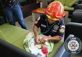 Un bombero de la estación 5 municipal práctica una evaluación médica a la menor que fue abandonada en la vía pública. (Foto Prensa Libre: CBM)