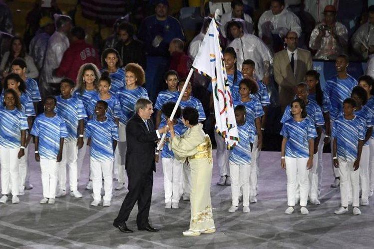 Thomas Bach (c), presidente del Comité Olímpico Internacional (COI), le entrega la bandera olímpica a la gobernadora de Tokio, Yuriko Koike (Foto Prensa Libre: AFP)
