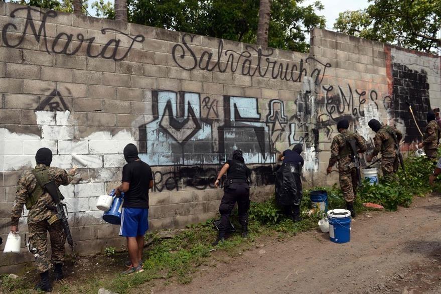 Oficiales de la Policía salvadoreña participan en una jornada para eliminar grafitis de los murales. (Foto Prensa Libre: AFP).