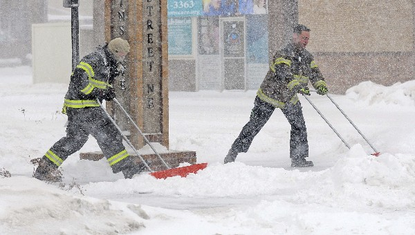 Bomberos limpian la acumulación de nieve frente a una vivienda en Dakota. (AP).