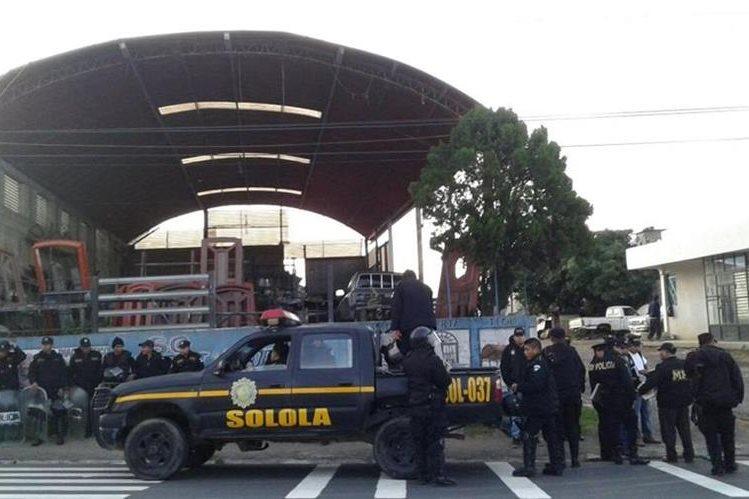 Agentes de la PNC acordonan taller de mecánica en Sololá, donde se efectuaron los allanamientos. (Foto Prensa Libre: PNC)