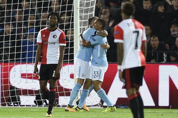 Gabriel Jesus y Nicolás Otamendi celebran un gol del Mánchester City, mientras los jugadores del Feyenoord se lamentan.