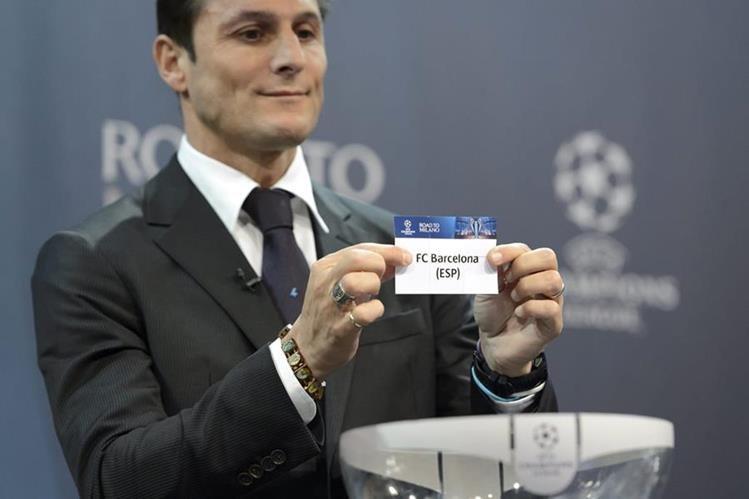 El exfutbolista argentino Javier Zanetti sostiene la papeleta del FC Barcelona que se enfrentará al Arsenal en los octavos de final de la Champions.(Foto Prensa Libre: EFE)