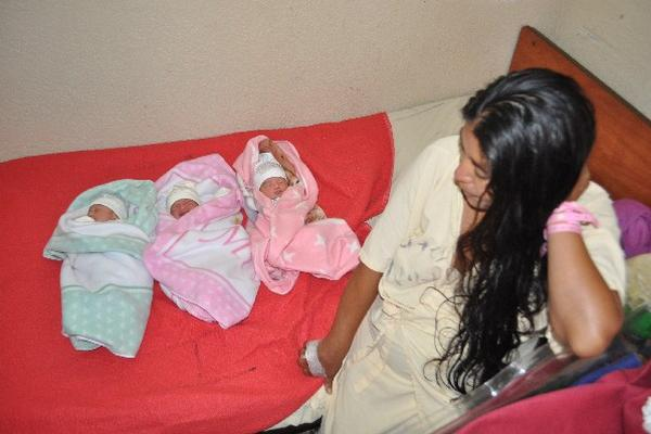 Madre observa a sus tres pequeñas hijas, en el Hospital Regional de  Huehuetenango.