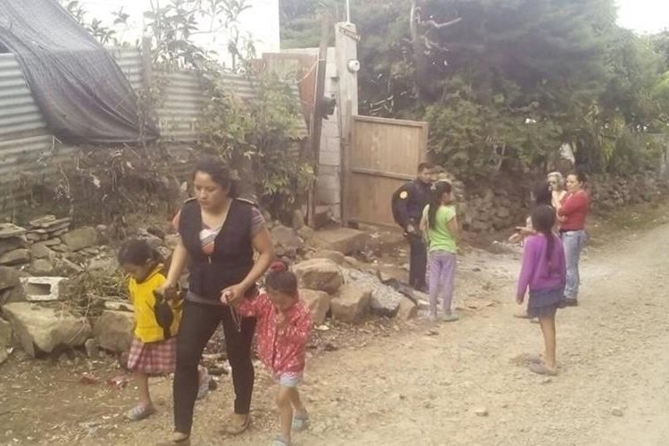 Una agente de la PNC acompaña a las niñas luego de ser encontradas en abandono en Palencia, Guatemala. (Foto Prensa Libre: Cortesía)