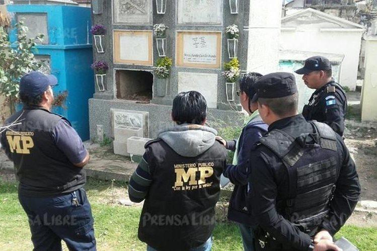 Investigadores observan tumba profanada en camposanto de Xela. (Foto Prensa Libre: Carlos Ventura).