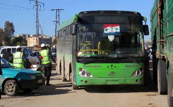 Un autobús recibe a los combatientes rebeldes y sus familias de las zonas de Alepo. (AFP).