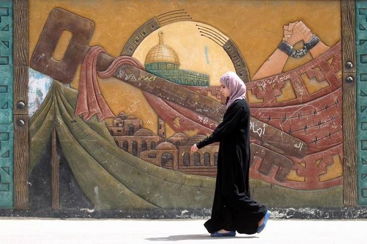 (Foto de referencia). Una palestina camina frente a un mural cerca de un campo de refugiados en Gaza. (Foto Prensa Libre: AFP).