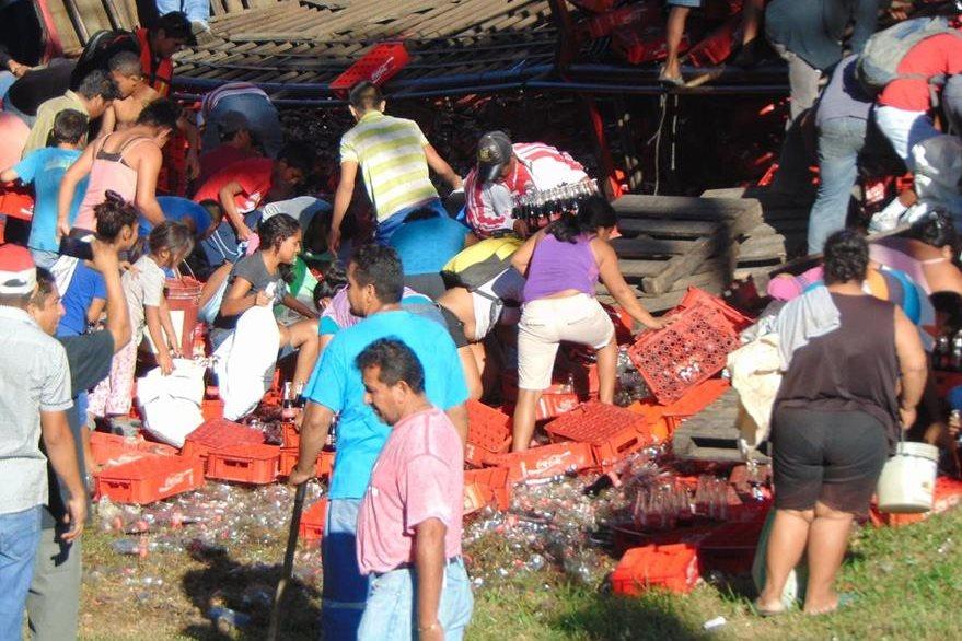 Vecinos de Escuintla toman cajas con bebidas que quedaron tiradas durante un accidente. (Foto Prensa Libre: Carlos E. Paredes)