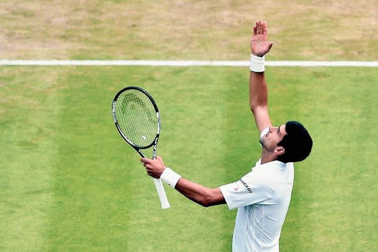 Novak Djokovic extiende los brazos en señal de triunfo luego de avanzar a los cuartos de final de Wimbledon. (Foto Prensa Libre: AFP)