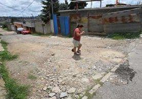Vecina de Santa Genoveva 3, zona 18, camina en la calle deteriorada que fue mejorada con recursos de los residentes. (Foto Prensa Libre: Estuardo Paredes)