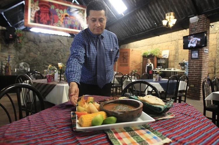 Marlon Hernández, gerente de Los Antojitos, muestra uno de los platos típicos que ofrecen. (Foto Prensa Libre: Carlos Hernández).