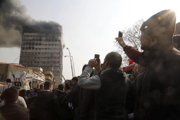 Curiosaos toman fotos frente al edificio en llasmas en Teherán, Irán.(EFE).