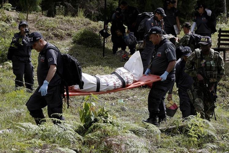 Forenses trasladan uno de los cadáveres hallados en la finca. (Foto Prensa Libre: EFE).