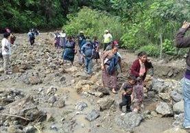 Varias personas caminan en el área del derrumbe de la ruta en el cerro Lec. (Foto Prensa Libre: Ángel Julajuj)
