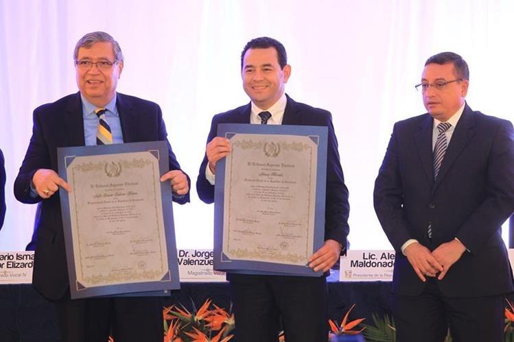 Jafeth Cabrera y Jimmy Morales, reciben de manos del Magistrado Rudy Pineda, el titulo que los acredita como presidente y vicepresidente electos de Guatemala (Foto Prensa Libre: HemerotecaPL)
