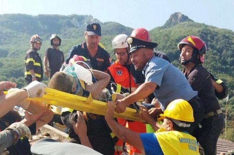 Miembros de los servicios de rescate tras localizarl al joven Mattias entre los escombros tras el terremoto en la isla Ischia en Italia. (Foto Prensa Libre: EFE)