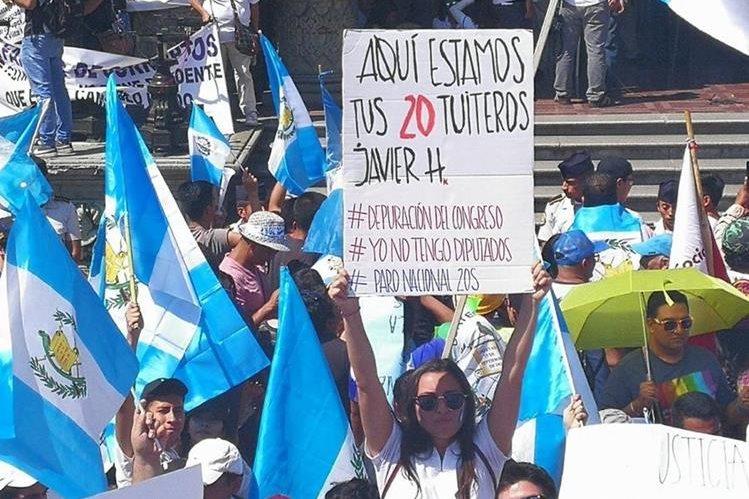 Guatemalteca muestra cartel con mensaje para el Congreso. (Foto Prensa Libre: Estuardo Paredes)