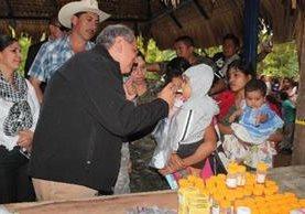El embajador Arnold Chacón  suministra una dosis de  desparasitante a un niño  de Camotán.