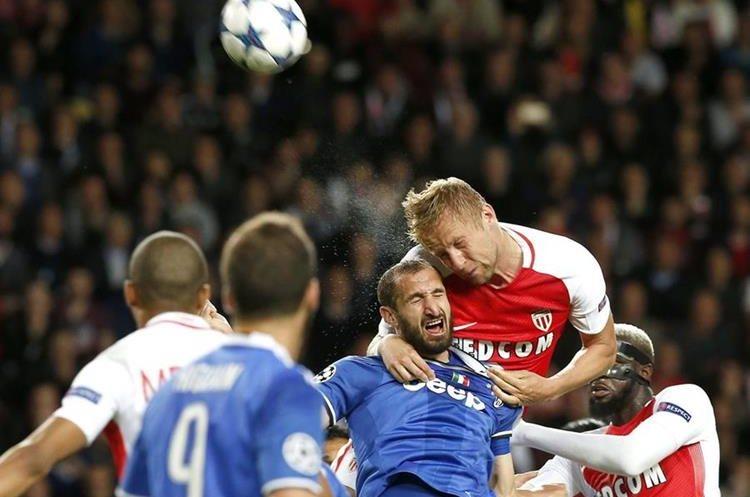 Kamil Glik del Mónaco intenta un remate de cabeza frente al italiano Giorgio Chiellini.