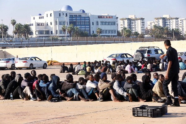 Autoridades libias vigilan a algunos de los 220 refugiados que han sido interceptados cuando trataban de llegar a las costas europeas en el puerto de Trípolo.