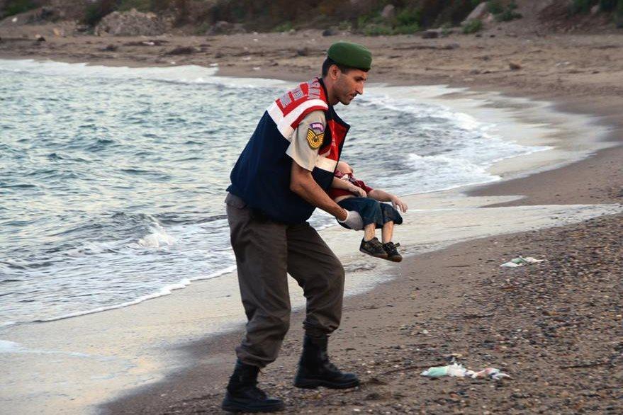 Un policía traslada el cuerpo del pequeño niño sirio de 3 años ya muerto. La estampa es una de las que conmocionó a Europa. (Foto Prensa Libre: AP).